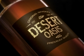 Label design with desert rock font as a headline on a whiskey bottle mockup